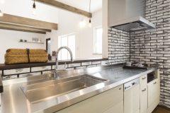 オリジナルキッチンと石調の壁面タイル