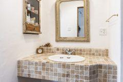 石材で仕上げた造作洗面台にアンティークの鏡と埋込のサイド収納